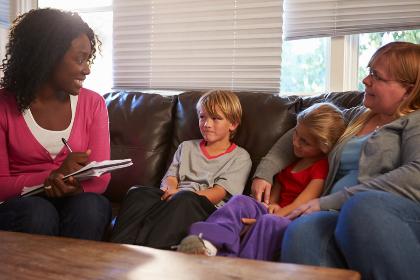 Social Worker Talking To Mother And Children At Home