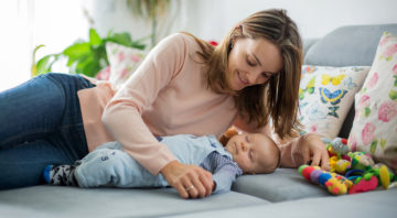 Cute baby boy and his mother, lying on the couch in living room, playing with toys, activity for early infant development