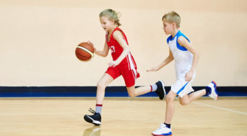 Girl and boy athlete in sport uniform playing basketball